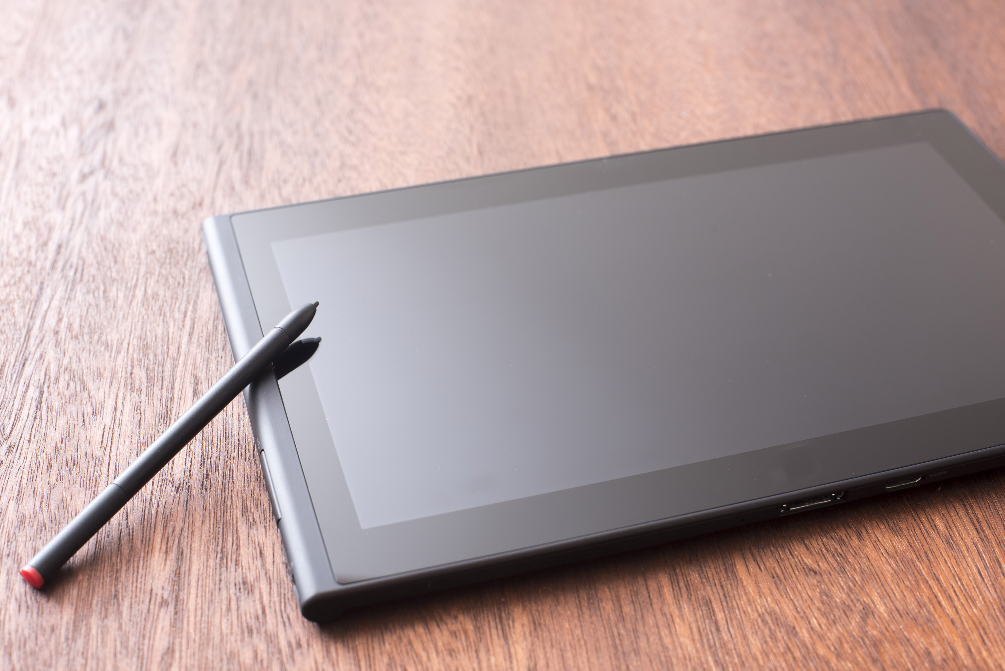 Blank digital tablet with a stylus resting on the side lying on a wooden desk in an oblique angle view