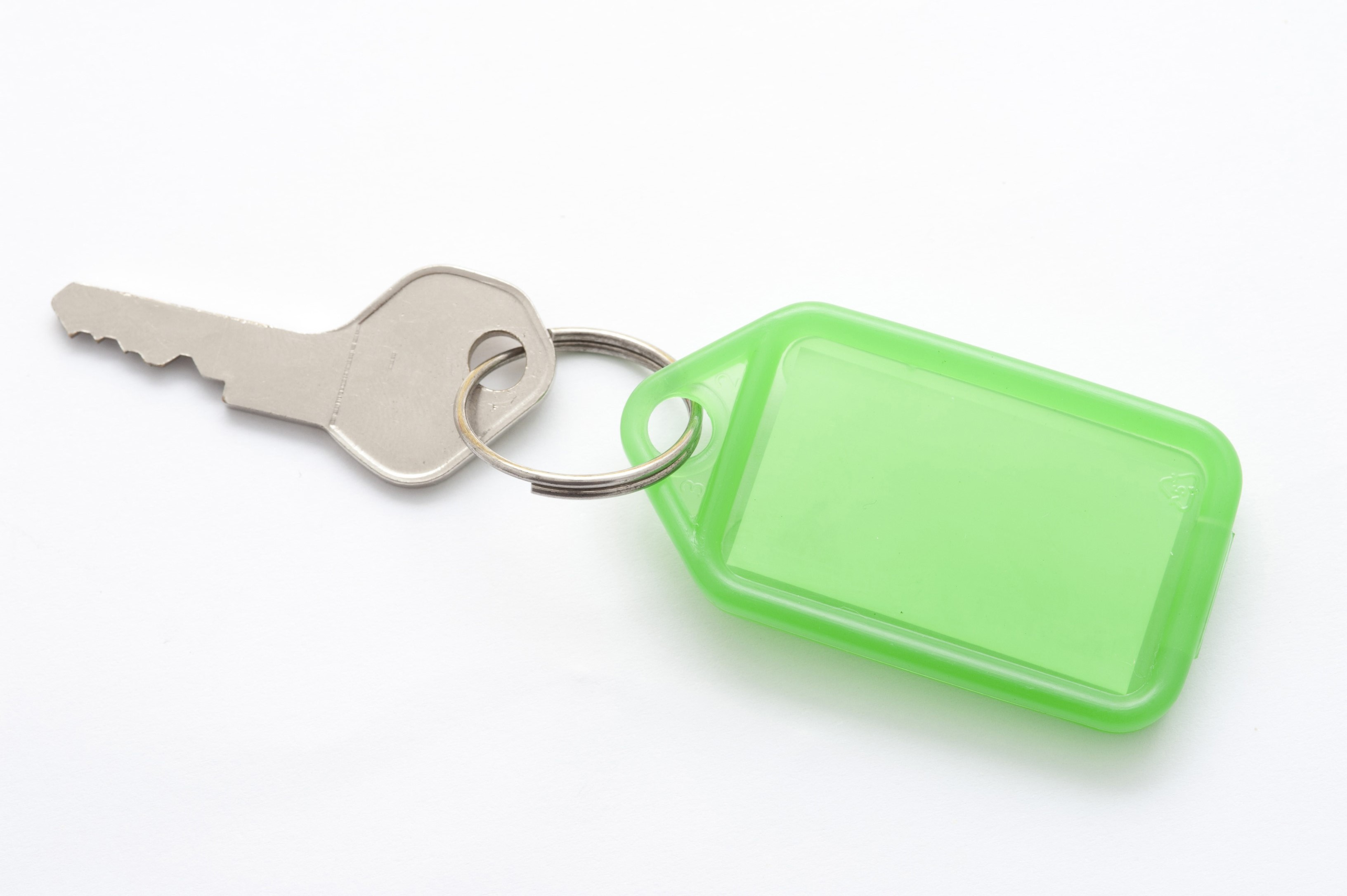 Small silver metal key attached to a blank green plastic key tag with copyspace for your text, on a white background