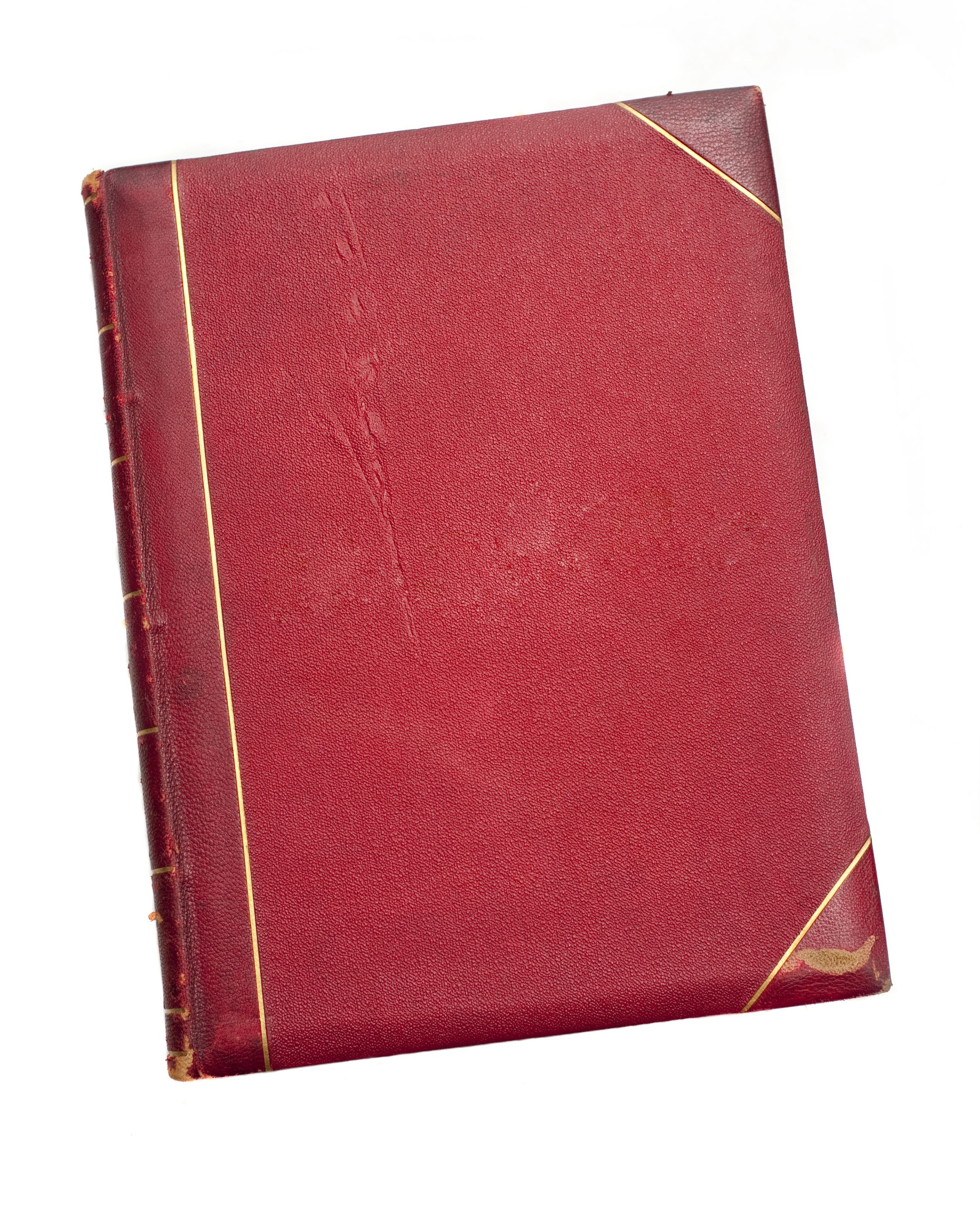 Old scuffed red book with leather binding and gilt tooling lying isolated on a white surface