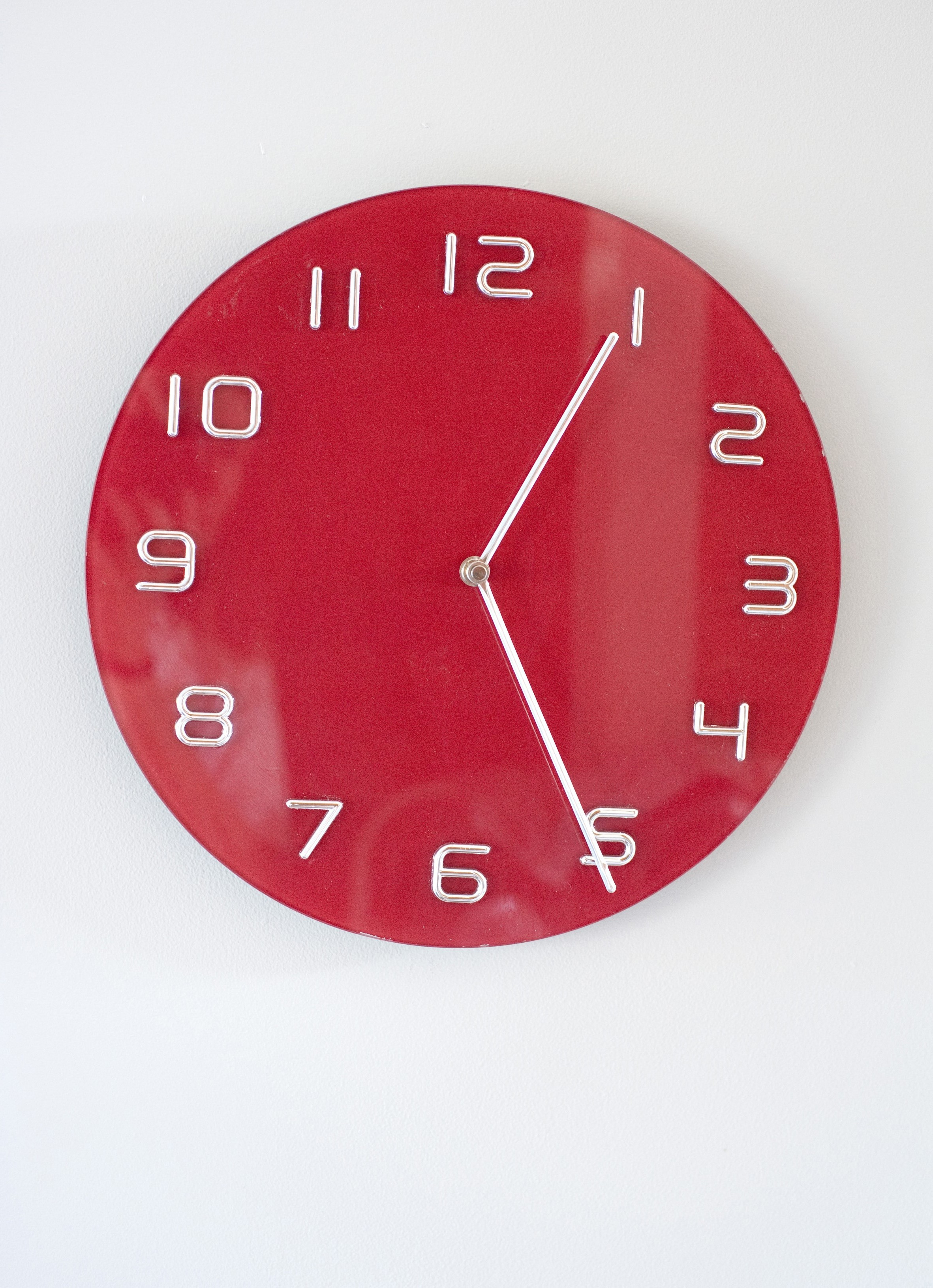 Modern simple circular red clock with Arabic numerals mounted on a white wall with copyspace