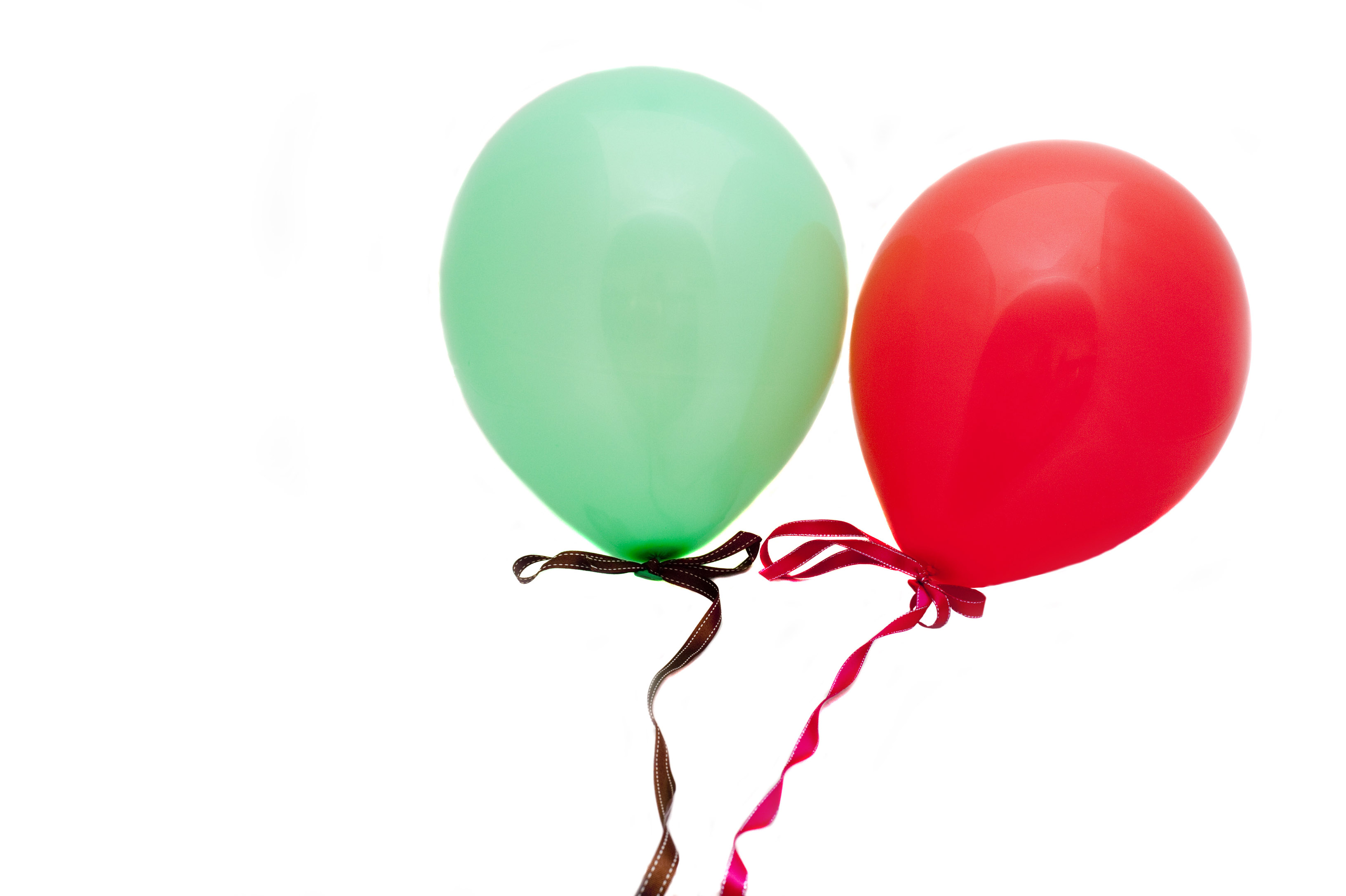 red and green party baloons on white background