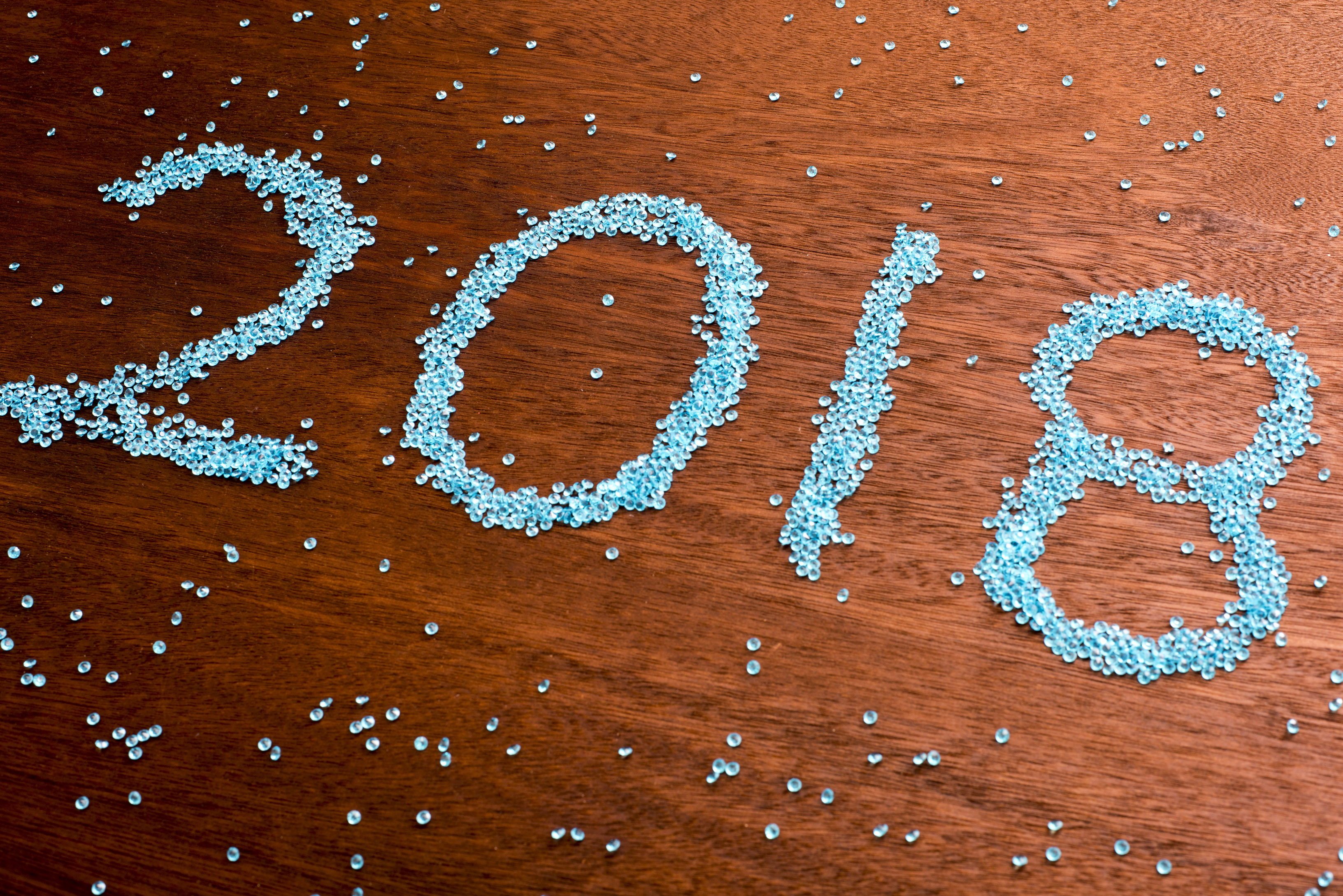 2018 New Year date in blue sequins on wood for a festive celebration of the holiday season in an angle view with copy space