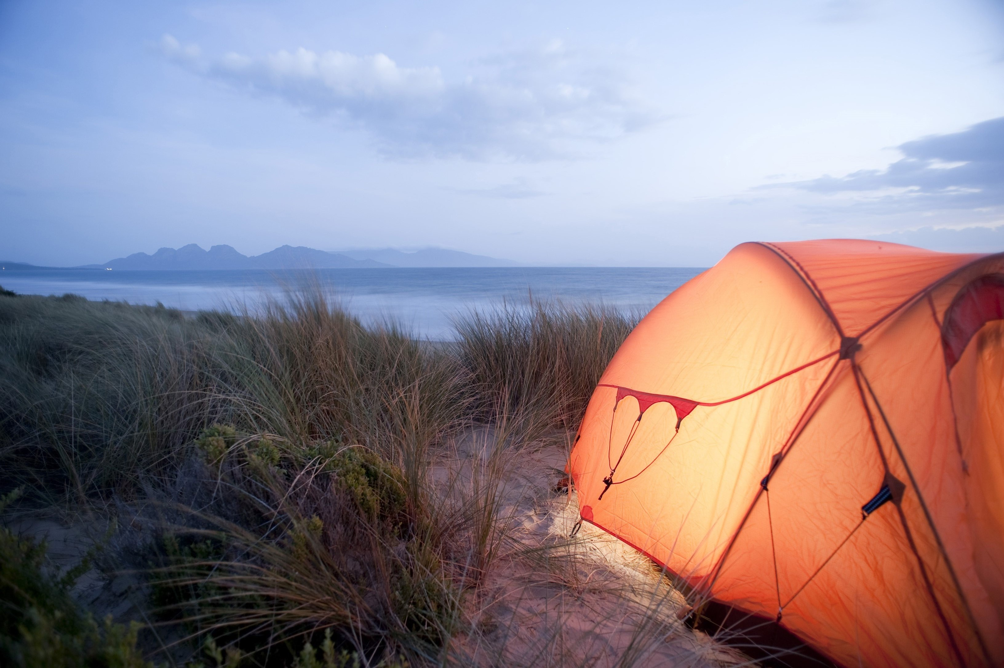 Camping tent pitched overlooking a distant marine bay illuminated at night from inside glowing in the evening light with copyspace