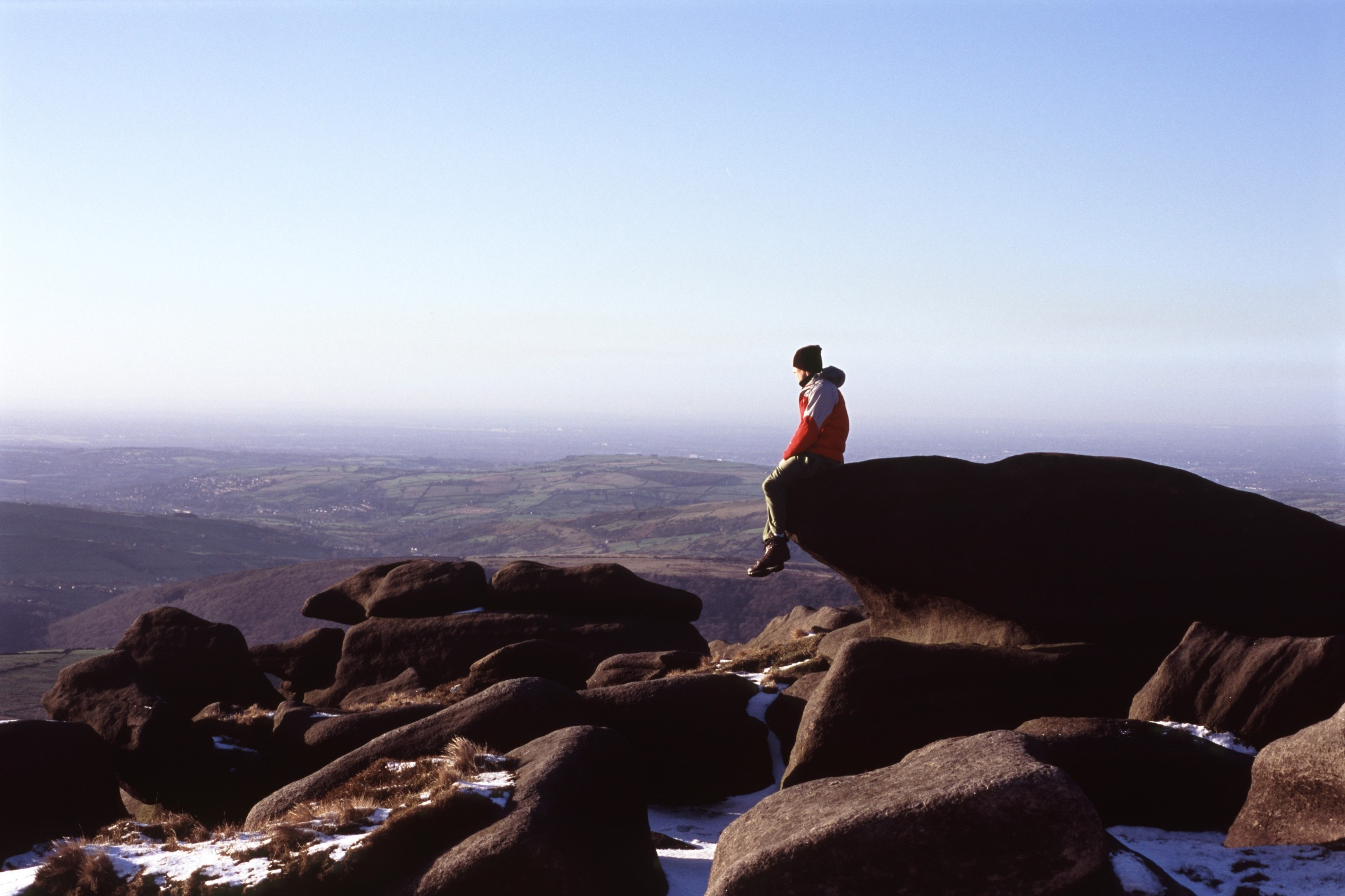 Lone figure of a man sitting on a mountain peak on the edge of a rock with scattered snow overlooking mountain ranges and valleys as he contemplates nature