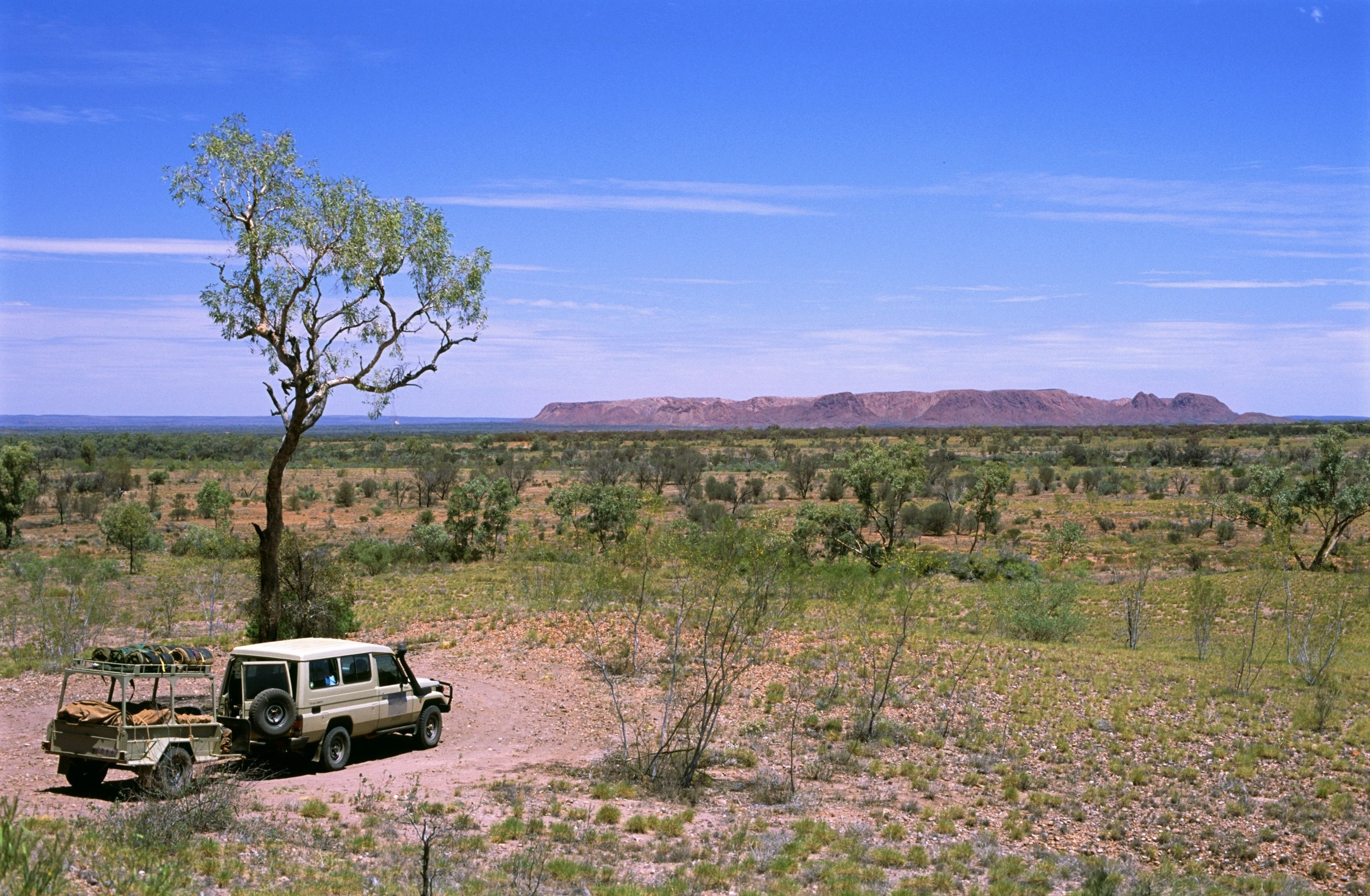 4x4 vehicle towing a trailer parked under a small tree overlooking an expanse of beautiful scenic countryside while out enjoying an Australian outback safari