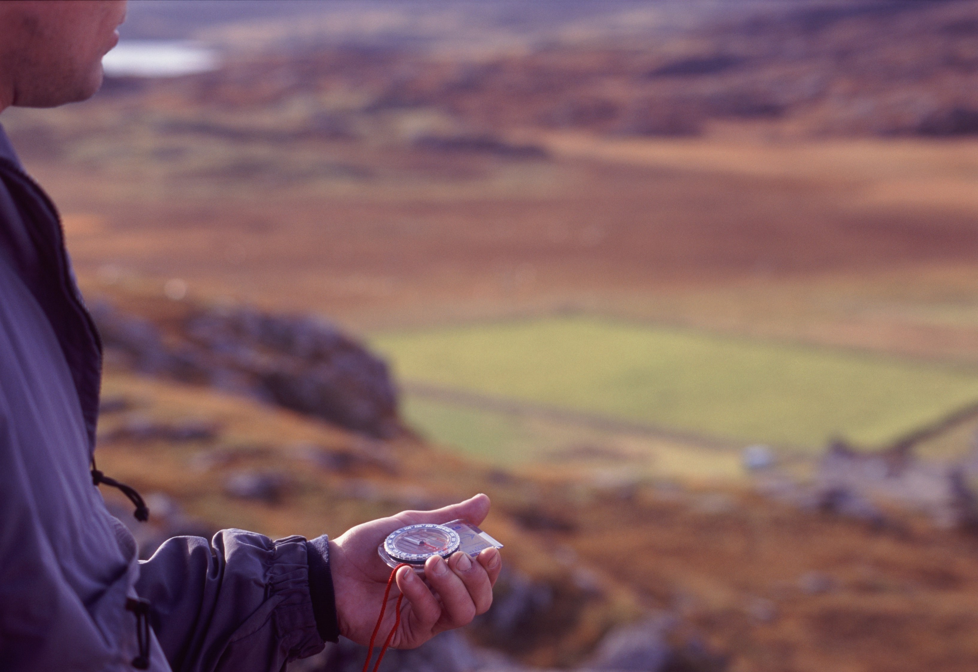 Wilderness navigation with a partial closeup view of a man holding a magnetic compass showing him the direction of magnetic north so that he can navigate to his destination