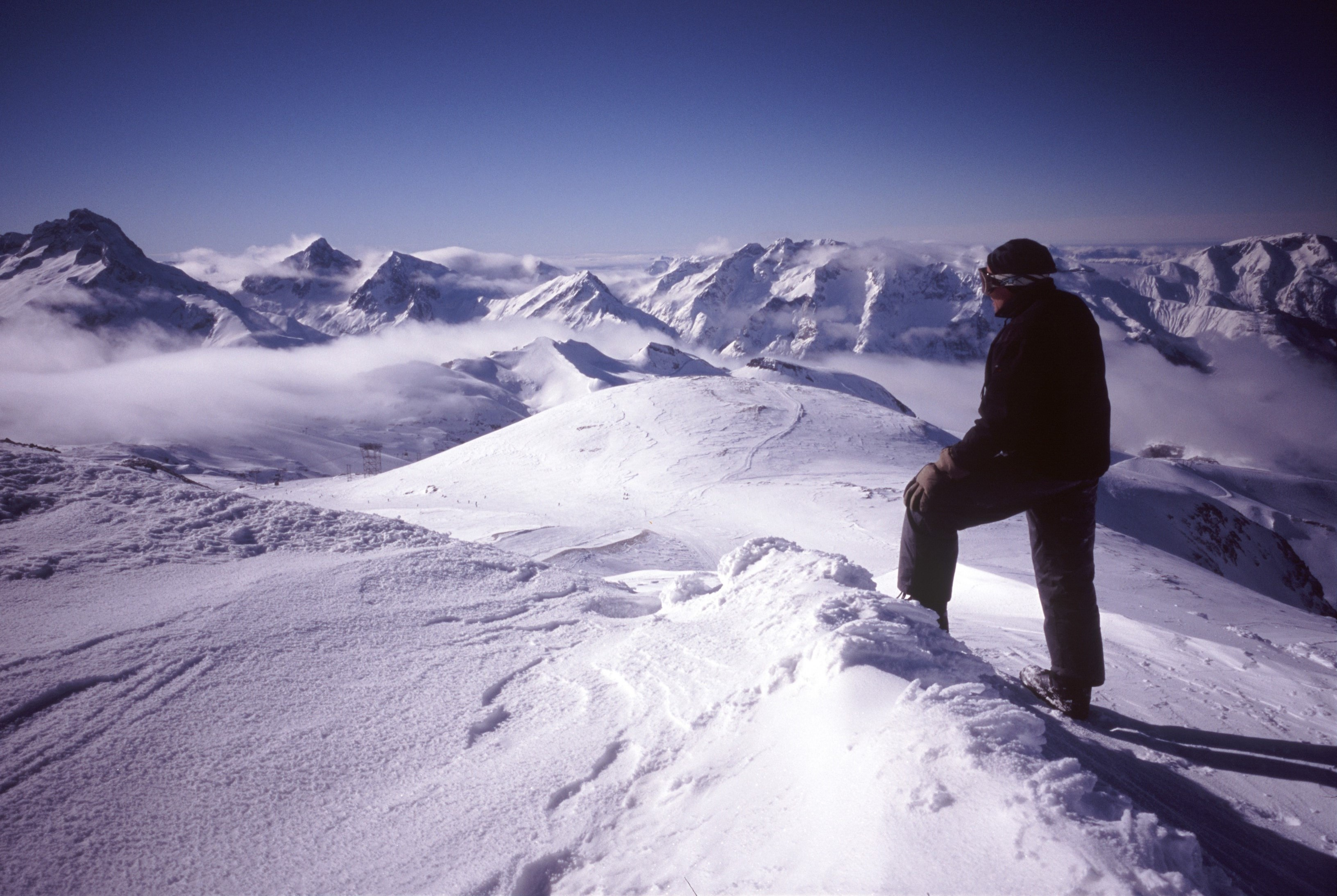 Man standing on heavy snow on a mountain peak looking out across a beautiful winter wonderland of snowcovered mountain ranges and peaks under a dense covering of fresh pristine white snow